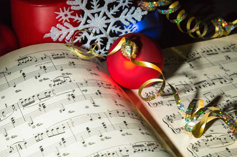 Sheet music with holiday ribbons, balls and a snowflake ornament.