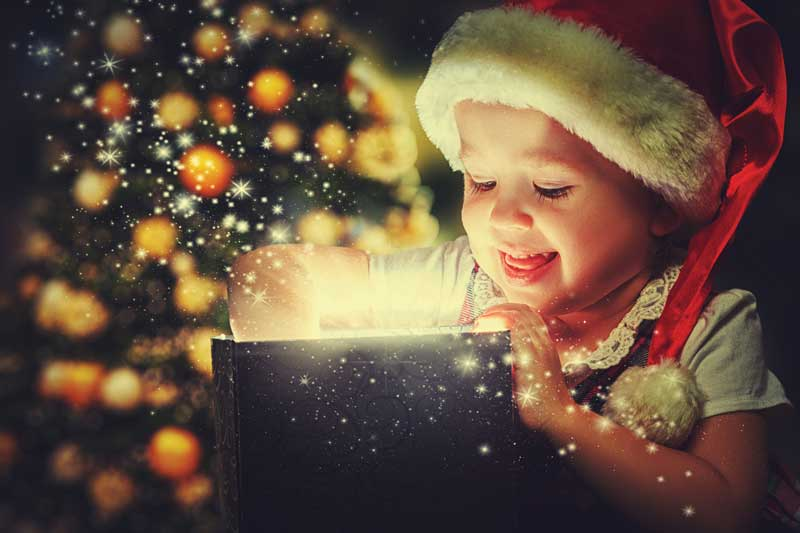 Young child opening a present that is glowing with light. Christmas tree in the background.