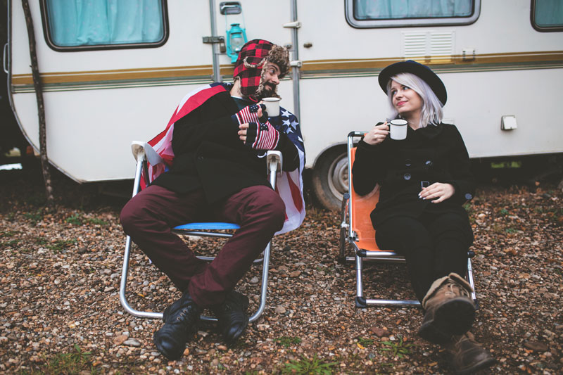 Hip Couple drinking coffee in front of an RV.
